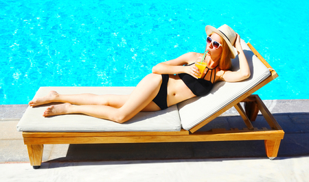 Summer holidays - pretty young woman resting with juice from cup on deckchair, blue water pool background Stock Photo