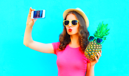Cool girl taking picture self portrait on smartphone with pineapple wearing straw hat over colorful blue background