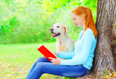Owner woman is reading a book with Golden Retriever dog sitting near a tree in the park
