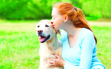 Happy owner woman is hugging kiss Golden Retriever dog on the grass