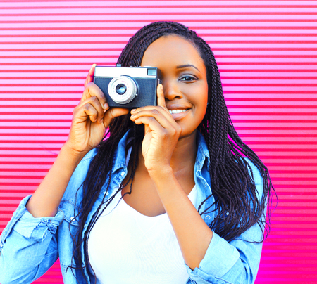 Happy african woman with old vintage camera over pink background