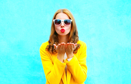 Beautiful woman sends an air kiss in yellow coat on colorful blue background close-up Фото со стока
