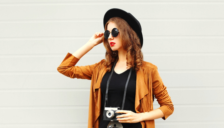 Fashion woman with retro film camera in black round hat, brown jacket on gray wall background