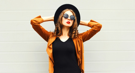 Mode vrouw in zwarte ronde hoed, zonnebril, jas op grijze muur achtergrond