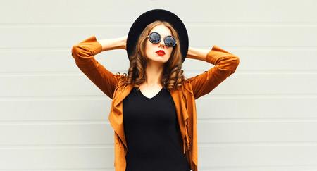 Mujer de moda con sombrero redondo negro, gafas de sol, chaqueta sobre fondo de pared gris