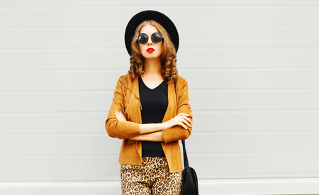 Beautiful woman in black round hat, sunglasses, brown jacket walking in city on gray wall background Фото со стока