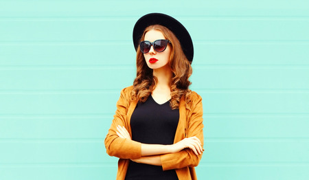 Fashion portrait young woman in black round hat, sunglasses posing on gray wall background Фото со стока