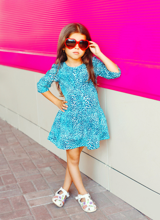 Beautiful little girl in leopard print dress on colorful pink background