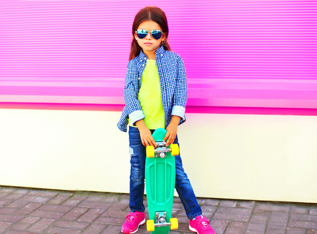 Fashion child little girl holds skateboard on pink wall background