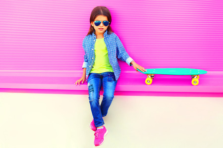 Fashion little girl child sitting with skateboard in city on colorful pink wall background