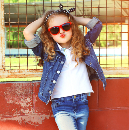 Fashion portrait little girl child in jeans jacket, red sunglasses posing in summer day