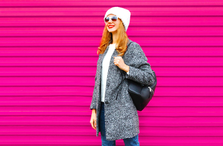 Young smiling woman wearing gray coat, hat, backpack walking in city on colorful pink wall background