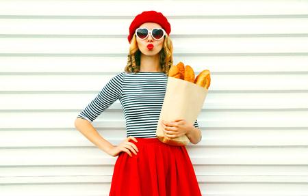 Portrait belle jeune femme soufflant des lèvres faisant un baiser d'air portant un béret rouge tenant dans les mains un sac en papier avec une longue baguette de pain blanc sur fond de mur blanc