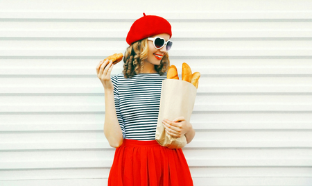 Pretty smiling young woman wearing red beret holding croissant, paper bag with a long white bread baguette on white wall background
