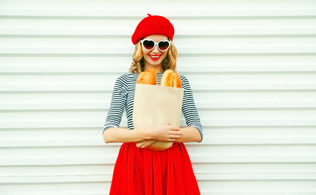 Happy smiling young woman wearing red beret holding paper bag with a long white bread baguette on white wall background Фото со стока