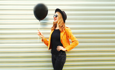 happy smiling woman looking at black helium air balloon in round hat, yellow jacket on metal wall background