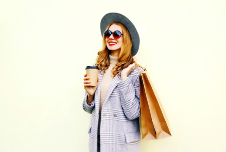 Portrait happy smiling woman with shopping bags, holding coffee cup, wearing pink coat, round hat on wall background