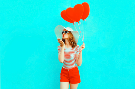 Beautiful young woman with red heart shaped balloons sending sweet air kiss on colorful blue background Standard-Bild