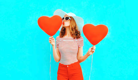 Beautiful young woman with red heart shaped balloons sending sweet air kiss on colorful blue background Stok Fotoğraf