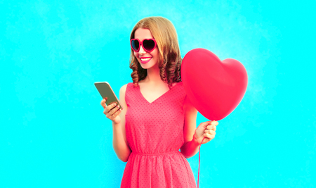Happy smiling young woman with phone, pink heart shaped air balloons on colorful blue background Standard-Bild