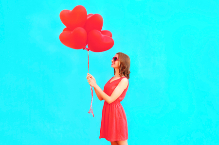 Happy woman holds red heart shaped air balloons on blue background