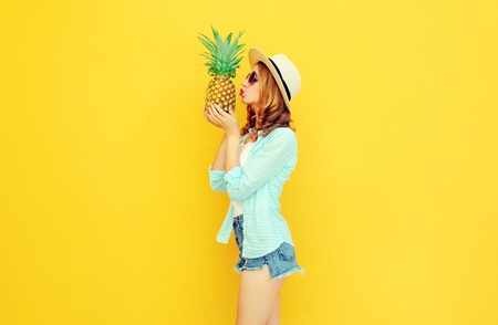 Beautiful young woman kissing tropical pineapple in summer straw hat, shorts on colorful yellow background