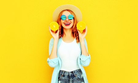 Summer portrait happy smiling woman holding in her hands slices of orange in straw hat on colorful yellow background