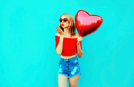 Portrait beautiful young woman sending sweet air kiss with red heart shaped balloon on colorful blue background Stock Photo