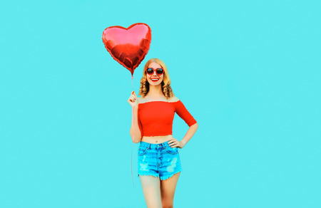 happy smiling woman holding red heart shaped air balloon on colorful blue background
