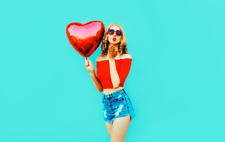 beautiful young woman sending sweet air kiss with red heart shaped balloon on colorful blue background
