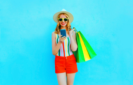 Portrait happy smiling woman holding smartphone with shopping bags in colorful t-shirt, summer straw hat, sunglasses, red shorts on blue background