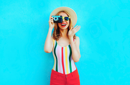 Colorful happy smiling young woman holding retro camera in summer straw hat having fun on blue wall background Banco de Imagens