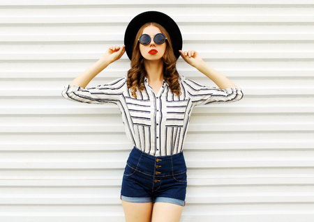 Stylish young woman model in black round hat, shorts, white striped shirt posing on white wall background