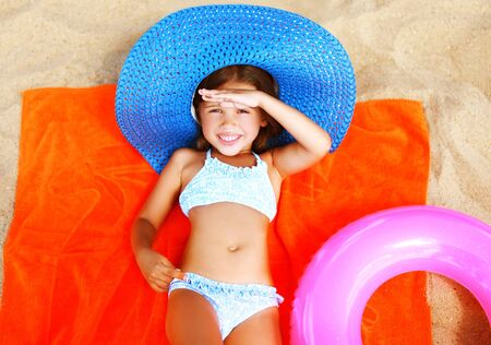Summer portrait little girl in bikini, straw hat lying sunbathing on sand beach 스톡 콘텐츠