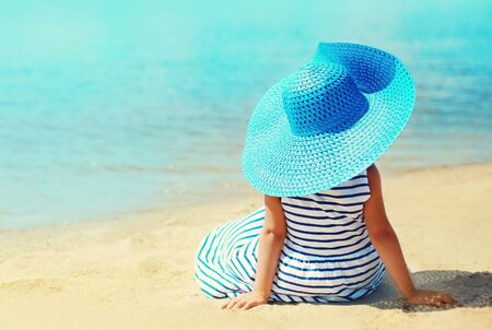 Summer holidays and vacation concept - little girl in striped dress, straw hat enjoying sitting on sand beach near sea Фото со стока
