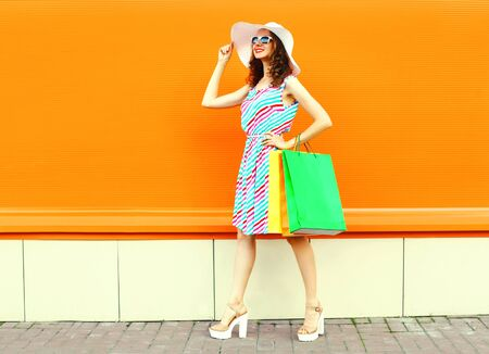 Stylish smiling woman with shopping bags wearing colorful striped dress, summer straw hat walking over orange wall background