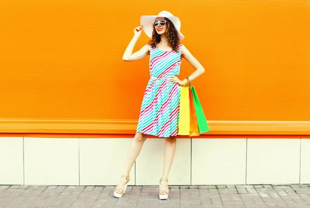 Stylish smiling woman with shopping bags wearing colorful striped dress, summer straw hat posing on orange wall background Stock Photo
