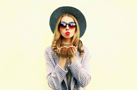 Portrait young woman blowing red lips sending air kiss in round hat on background Stok Fotoğraf - 132051187