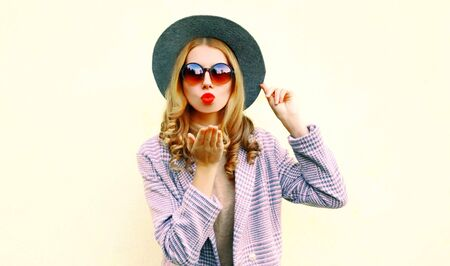 Portrait young woman blowing red lips sending air kiss in round hat on background
