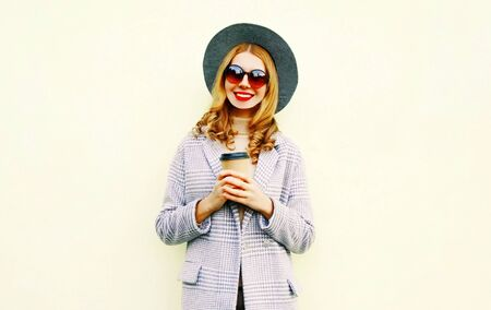 Portrait happy smiling woman with coffee cup in pink coat, round hat on wall background