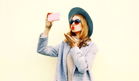 Beautiful woman taking selfie picture by smartphone blowing red lips sending sweet air kiss in pink coat jacket, round hat, on wall background on city street
