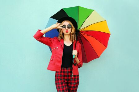 Stylish young woman with colorful umbrella blowing red lips sending sweet air kiss, wearing red jacket, black hat on blue wall background Stok Fotoğraf - 132051320