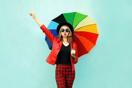 Stylish young woman with colorful umbrella blowing red lips sending sweet air kiss, wearing red jacket, black hat on blue wall background