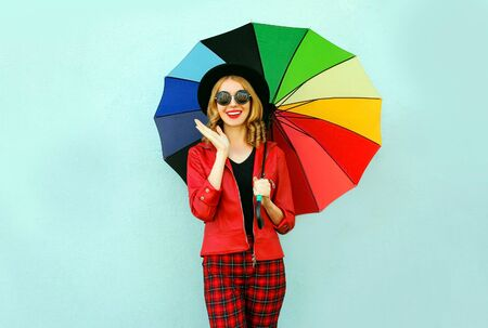 Happy young surprised woman with colorful umbrella, wearing red jacket, black hat on blue wall background
