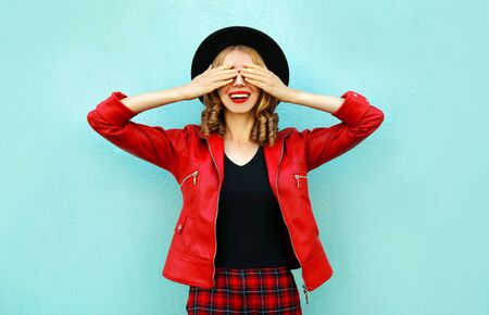 Happy smiling woman closes her eyes with her hands, making a wish, wearing red jacket, black hat on blue wall background