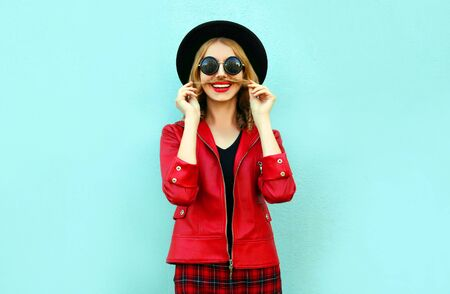 Portrait funny smiling woman showing moustache her hair in black round hat, red jacket on blue background
