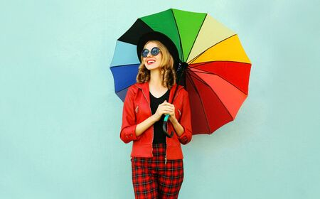 Happy smiling young woman holding colorful umbrella in hands, wearing red jacket, black hat on blue wall background