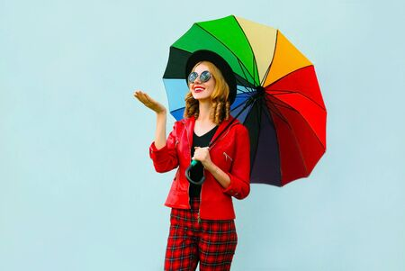 Happy smiling young woman holding colorful umbrella, checking with outstretched hand rain, wearing red jacket, black hat on blue wall background