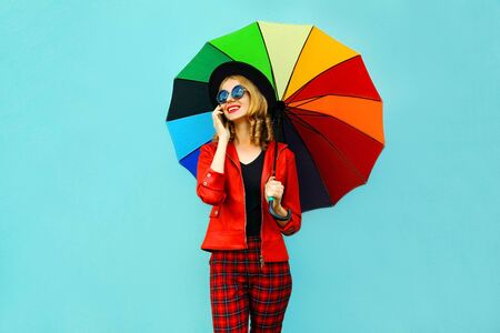 Portrait smiling young woman calling on phone with colorful umbrella in red jacket, black hat on blue wall background