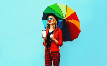 Young woman drinking coffee and holding colorful umbrella walking in red jacket, black hat on blue wall background